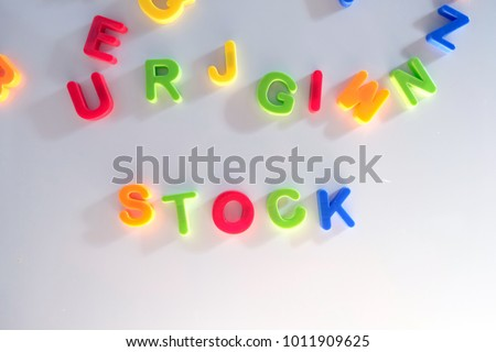 Color Letter magnets on a fridge with the sun coming in from the right stock