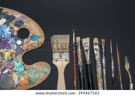 Color palette and brushes/Abstract view of some used painting utensils such as a color mixing palette, a few brushes in a variety of strokes and a palette knife, all covered in multi colored paint. - stock photo