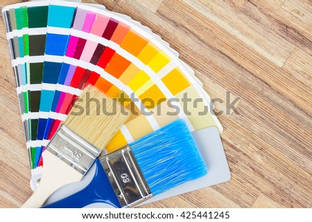 Color palette guide and brushes on wooden desktop - stock photo