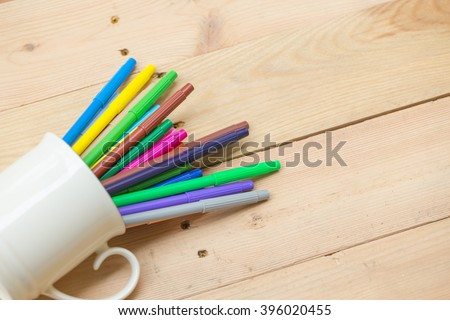 color pen on wood table background with copy space, artist working space concept. - stock photo