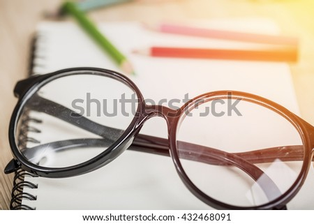 Color pencil and eyeglasses on table. Vintage filter