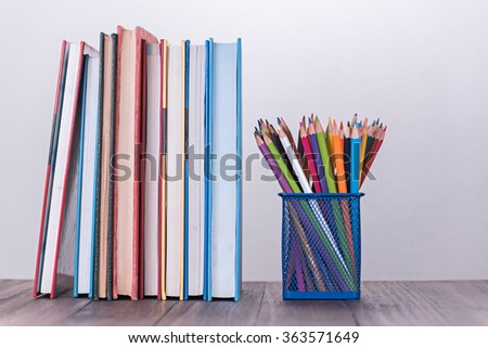 color pencil box and stack of book on wooden table - stock photo