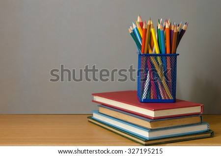 color pencil box on stack of book - stock photo