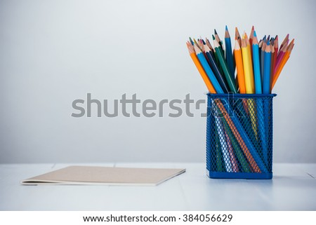 color pencil box on white wooden table - stock photo