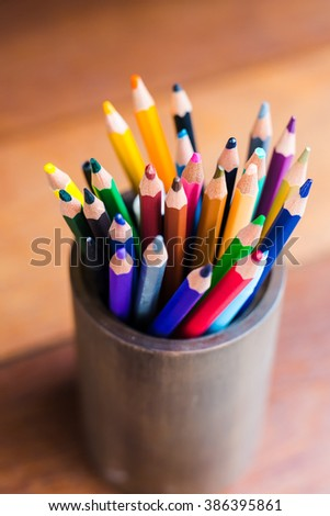 color pencil in box on wooden table - stock photo