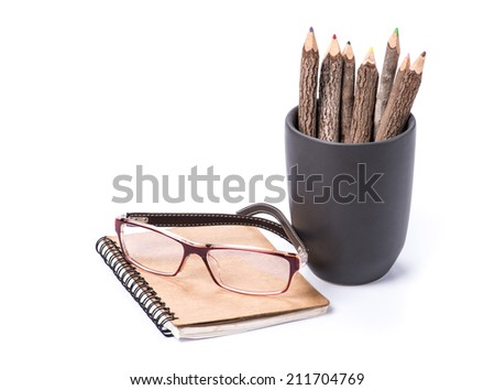 color pencil made of branches in cup with glasses and note book on white background - stock photo