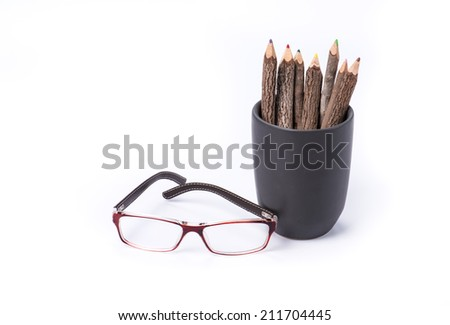 color pencil made of branches in cup with glasses on white background - stock photo