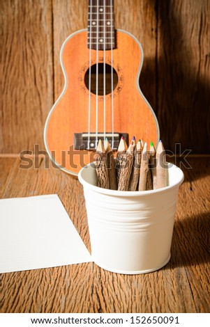 color pencil made of branches with paper and ukulele - stock photo