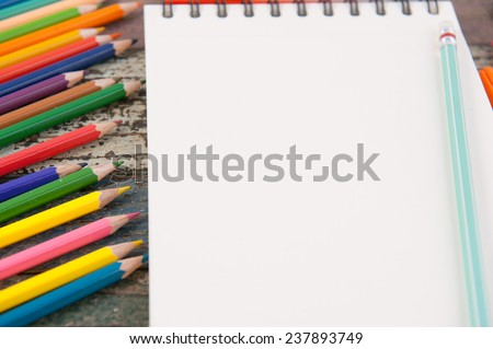 Color pencil on sketch book and vintage wood table for background and text - stock photo