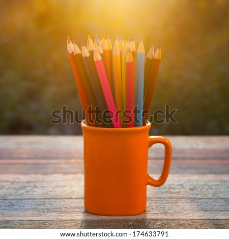 Color pencil on sketch book and vintage wood table in sunset - stock photo