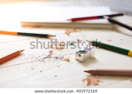 Color Pencil using a sharpener on wodden table - stock photo