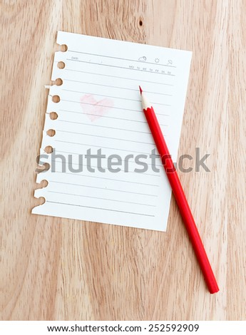 Color pencil with note paper on wooden