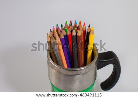 Color pencils and cup isolated on white background
