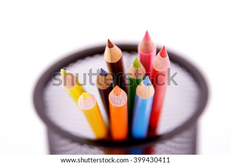 Color pencils in a pencil holder on white background