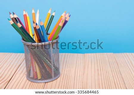 color pencils in pen holder on wooden table