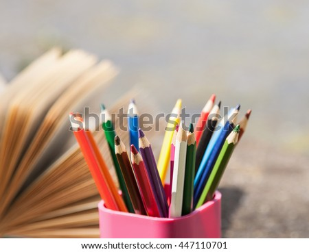Color pencils into the pencil holder and opened book, closeup shot - stock photo
