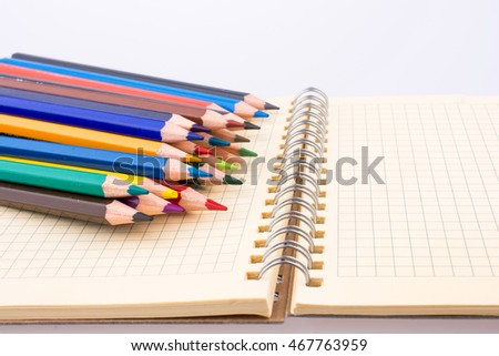 color pencils of various colors near a notebook on a white background