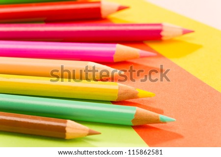 Color pencils on colorful papers close-up creativity concept