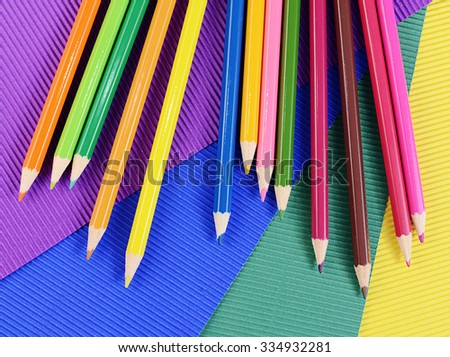 Color pencils on multi-colored paper close up - stock photo