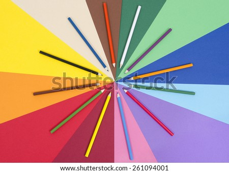 Color pencils on paper. All colors pencils arranged in a circle on rainbow color paper. - stock photo