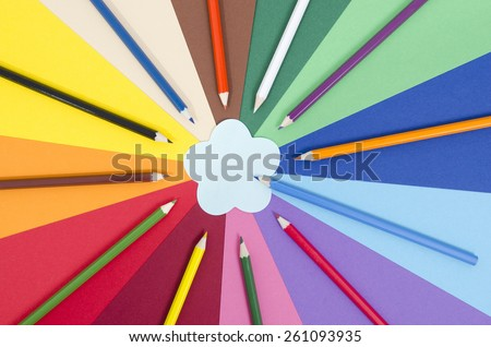 Color pencils on paper with flower memo note. All colors pencils arranged in a circle on rainbow color paper with blank post it note. - stock photo