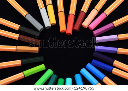 Color Pens in form of love on black background - stock photo