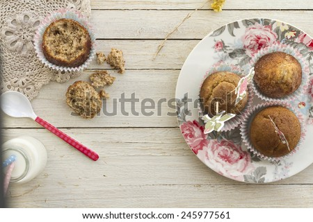 Color photo, decorative delicious breakfast with whole muffins on flowered dish accompanied by milk. - stock photo