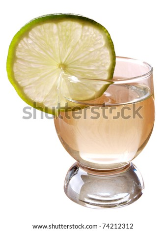 Color photo of a glass cup with tequila and lime