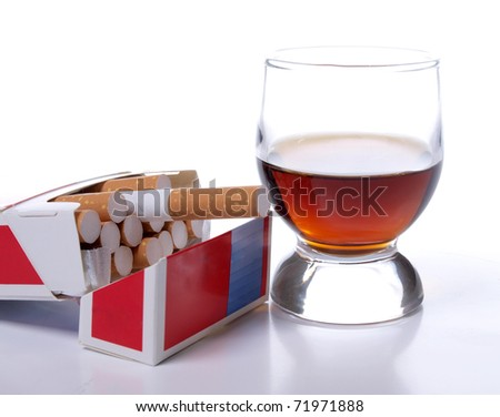 Color photo of a glass of whiskey and a pack of cigarettes - stock photo