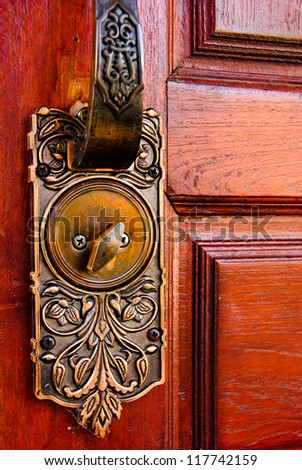 Color photo of a metal handle on a wooden door - stock photo