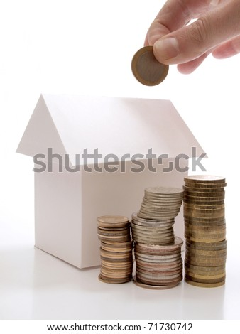 Color photo of a model home and coins - stock photo