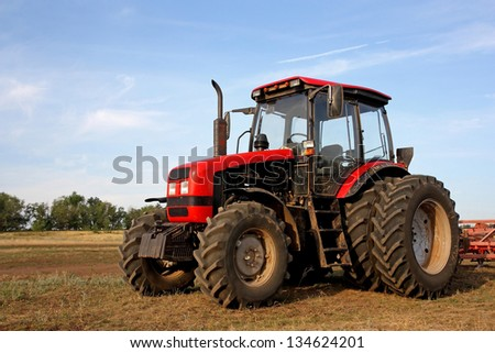 Color photo of a red tractor against the blue sky - stock photo