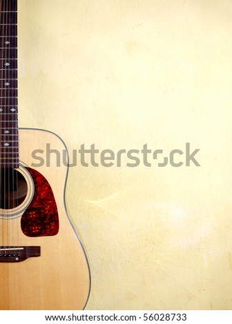 Color photo of an acoustic guitar near wall - stock photo