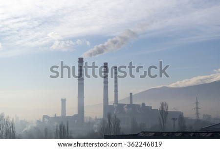 Color photograph of industrial buildings and mountain in background. - stock photo