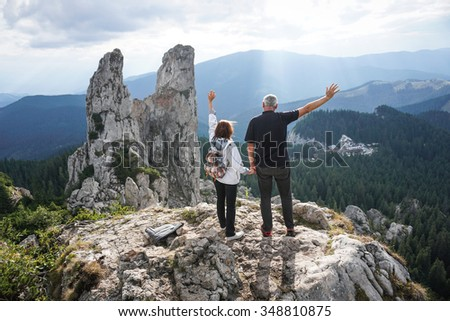 Color picture of an elderly couple holding hands and waving on top of a mountain - stock photo