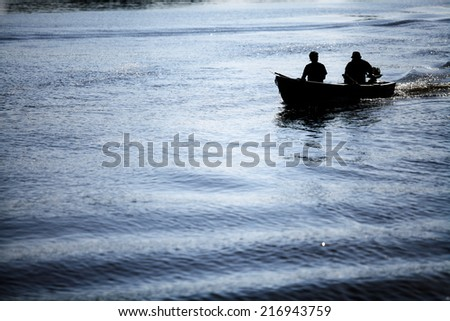 Color picture of people in a boat on a river.