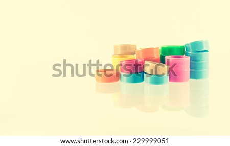 color plastic bottle caps with retro filter on white background - stock photo