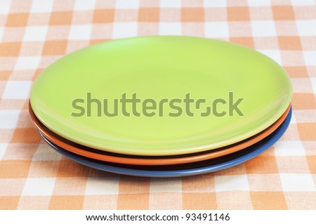 Color plates on the checkered tablecloth - stock photo