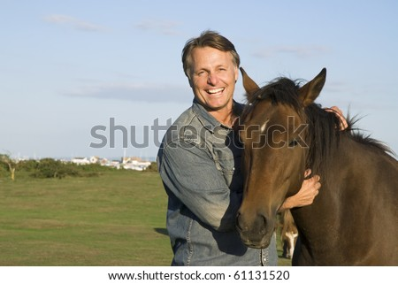 color portrait photo of a hppy smiling forties man petting his horse