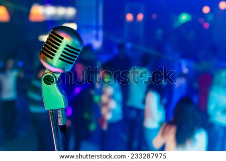 Color professional studio microphone in a night club. There are dancing people on background. - stock photo