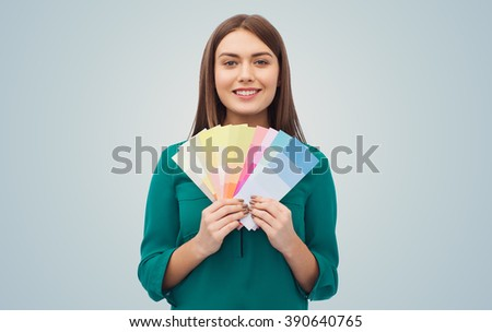color scheme, decoration, design and people concept - smiling young woman with color swatches or samples over gray background