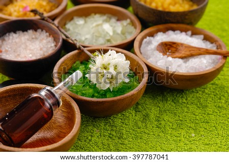 color sea salt in wooden bowl with spoon oil on green towel - stock photo