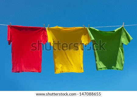 Color shirts on clothesline against blue sky. - stock photo