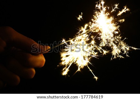 Color shot of a hand holding a sparkler - stock photo