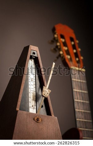 Color shot of a vintage metronome, next to an acoustic guitar, on a black background. - stock photo