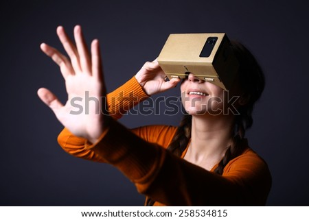 Color shot of a young woman looking through a cardboard, a device with which one can experience virtual reality on a mobile phone. - stock photo