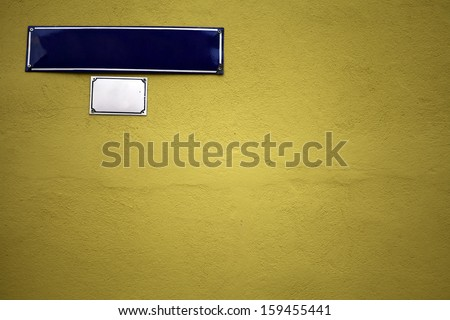 Color shot of an empty blue street sign on a green wall - stock photo