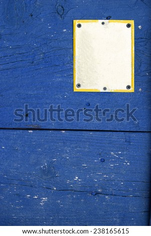 Color shot of an empty white sign on a blue wall. - stock photo