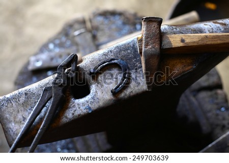Color shot with a hammer, a horse shoe and an anvil.  - stock photo
