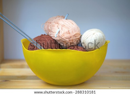 Color skeins of wool yarn, knitting needles and crochet hook in a big yellow bowl on wooden shelf. Photo closeup - stock photo